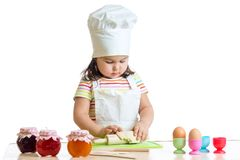 Little baker kid girl in chef hat at kitchen Royalty Free Stock Image