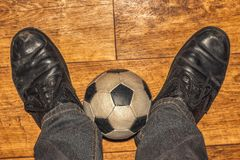 Football amateur. Little ball and black shoes , amateur footballer stock photography