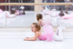 Little ballerina at ballet class. Little ballerina girl in a pink tutu. Adorable child dancing classical ballet in a white studio. Children dance. Kids stock photo