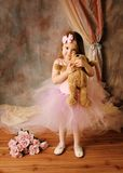 Little ballerina beauty. Adorable little girl dressed as a ballerina in a tutu, hugging a teddy bear standing next to pink roses Royalty Free Stock Photos