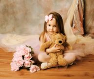 Little ballerina beauty. Adorable little girl dressed as a ballerina in a tutu, hugging a teddy bear sitting next to pink roses Royalty Free Stock Photography