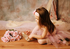 Little ballerina beauty. Adorable little girl dressed as a ballerina in a tutu, tying her ballet slippers Royalty Free Stock Photos