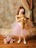 Little ballerina beauty. Adorable little girl dressed as a ballerina in a tutu, hugging a teddy bear standing next to pink roses Royalty Free Stock Photography