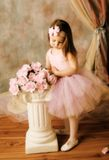 Little ballerina beauty. Adorable little girl dressed as a ballerina in a tutu standing next to pink roses Stock Images