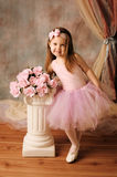 Little ballerina beauty. Adorable little girl dressed as a ballerina in a tutu standing next to pink roses Stock Photography