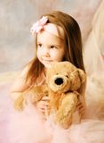 Little ballerina beauty. Adorable little girl dressed as a ballerina in a tutu and bow headband hugging a teddy bear Royalty Free Stock Image