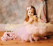 Little ballerina beauty. Adorable little girl dressed as a ballerina in a tutu, hugging a teddy bear sitting next to pink roses Royalty Free Stock Photo