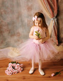 Little ballerina beauty holding a pink rose. Adorable little girl dressed as a ballerina in a tutu standing next to pink roses Stock Images