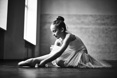 Little ballerina. Cute little ballerina in tutu tying up her shoes Stock Image