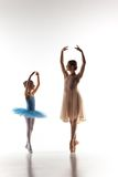 The little ballerina dancing with personal ballet teacher in dance studio. The silhouettes of little ballerina and personal classic ballet teacher in dance stock photography