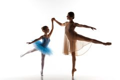 The little ballerina dancing with personal ballet teacher in dance studio. The silhouettes of little ballerina and personal classic ballet teacher in dance royalty free stock images