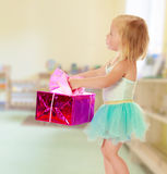 Little ballerina with a gift. Cute little girl in a ballerina costume, carrying on his outstretched hands a gift box.On the background of the room where children Stock Images