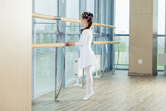 Little ballerina girl. Adorable child dancing classical ballet in a white studio. Stock Image