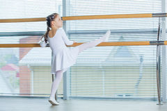 Little ballerina girl. Adorable child dancing classical ballet in a white studio. Stock Photos
