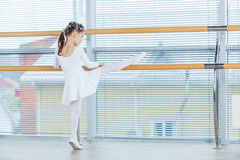 Little ballerina girl. Adorable child dancing classical ballet in a white studio. Stock Images