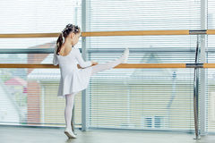 Little ballerina girl. Adorable child dancing classical ballet in a white studio. Stock Photo
