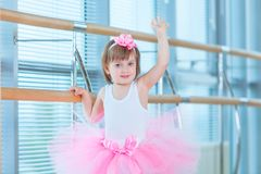 Little ballerina girl in a pink tutu. Adorable child dancing classical ballet in a white studio. Children dance. Kids. Performing. Young gifted dancer in a Stock Photography