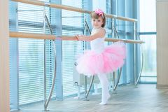 Little ballerina girl in a pink tutu. Adorable child dancing classical ballet in a white studio. Children dance. Kids. Performing. Young gifted dancer in a royalty free stock images