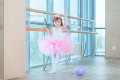 Little ballerina girl in a pink tutu. Adorable child dancing classical ballet in a white studio. Children dance. Kids. Performing. Young gifted dancer in a Royalty Free Stock Photos
