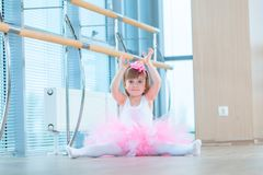Little ballerina girl in a pink tutu. Adorable child dancing classical ballet in a white studio. Children dance. Kids stock photo