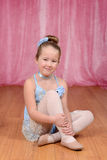 Little ballerina girl sitting on stage Royalty Free Stock Images