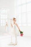 Little ballerina girl in a tutu. Adorable child dancing classical ballet in a white studio. Stock Photo