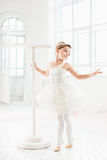 Little ballerina girl in a tutu. Adorable child dancing classical ballet in a white studio. Royalty Free Stock Image