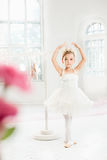 Little ballerina girl in a tutu. Adorable child dancing classical ballet in a white studio. Royalty Free Stock Photo