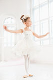 Little ballerina girl in a tutu. Adorable child dancing classical ballet in a white studio. Royalty Free Stock Photography