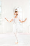 Little ballerina girl in a tutu. Adorable child dancing classical ballet in a white studio. Stock Photography