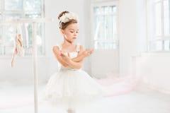 Little ballerina girl in a tutu. Adorable child dancing classical ballet in a white studio. Stock Photos