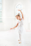 Little ballerina girl in a tutu. Adorable child dancing classical ballet in a white studio. Royalty Free Stock Photos