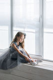 Little ballerina in gray dress puts on ballet shoes pointe front Royalty Free Stock Image