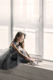 Little ballerina in gray dress puts on ballet shoes pointe front Royalty Free Stock Images