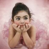 The Little Ballerina. With a pensive look on a pink background Stock Image