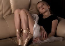 Little ballerina in pointe sits and resting on the sofa. cute ballerina in the dance class is studying ballet. Classical. Dance, ballet stock photo