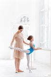 The little ballerina posing at ballet barre with personal teacher in dance studio. The little ballerina in tutu with personal classic ballet teacher in dance royalty free stock photo