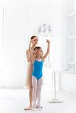 The little ballerina posing at ballet barre with personal teacher in dance studio Stock Photography