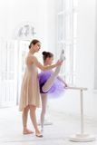The little ballerina posing at ballet barre with personal teacher in dance studio. The little ballerina in tutu with personal classic ballet teacher in dance stock image