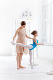 The little ballerina posing at ballet barre with Royalty Free Stock Photography