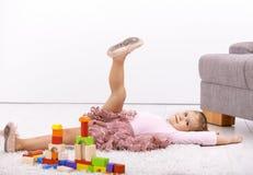Little ballerina posing on floor. Little ballerina girl laying on floor at home, playing, posing royalty free stock photos