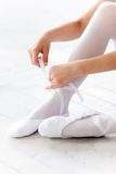 Little ballerina puting on foot pointe shoes Royalty Free Stock Images