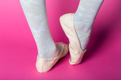 Little ballerina`s legs. In pointe on a pink background. ballet position stock images