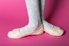 Little ballerina`s legs. In pointe on a pink background. ballet position stock image