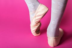 Little ballerina`s legs. In pointe on a pink background. ballet position stock photography