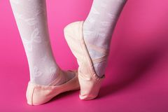 Little ballerina`s legs. In pointe on a pink background. ballet position stock photo
