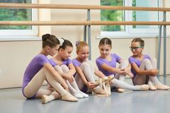 Little ballerina showing her ballet shoes to colleagues. Royalty Free Stock Photo