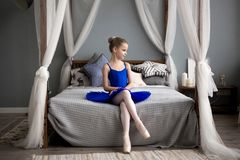 Little ballerina sitting on a bed. Cute little girl dreams of becoming a ballerina. Little ballerina sitting on a bed. little girl dreams of becoming a Royalty Free Stock Photo