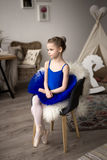 Little ballerina. Sitting on a chair Royalty Free Stock Photography