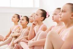 Little ballerinas in ballet studio. Group of girls having break in practice, sitting on floor. Classical dance school Stock Photo